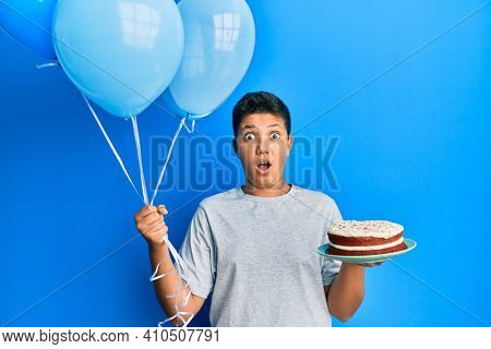 Teenager hispanic boy celebrating birthday with cake holding balloons afraid and shocked with surprise and amazed expression, fear and excited face.