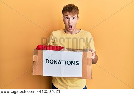Young caucasian man holding donations box for charity afraid and shocked with surprise and amazed expression, fear and excited face.