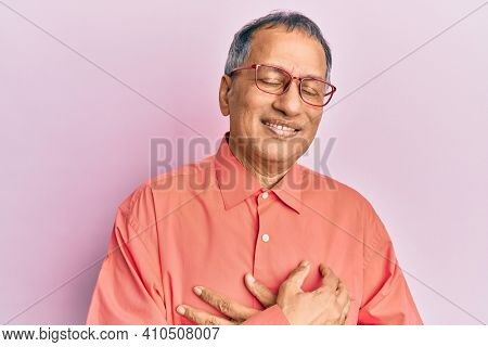 Middle age indian man wearing casual clothes and glasses smiling with hands on chest with closed eyes and grateful gesture on face. health concept.