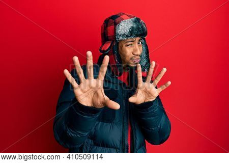 Young african american man with beard wearing winter hat and coat disgusted expression, displeased and fearful doing disgust face because aversion reaction. with hands raised