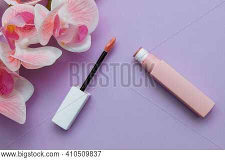 Pink Matte Liquid Lipstick, Open Brush On Purple Background With Orchid Flowers Close-up Flat Compos