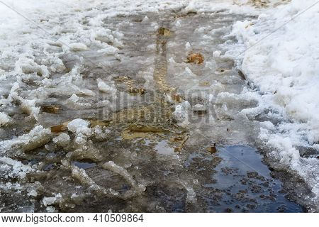 Slush.huge Children's Puddle On The Playground.asphalt Road Covered With Melting Dirty Snow And Mud.