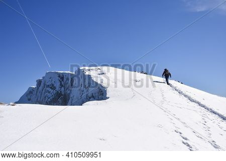 Lonely Mountaineer Hiking On Snowy Mountain Into The Sun. Climber High In Snowy Mountains