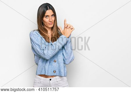 Young woman wearing casual clothes holding symbolic gun with hand gesture, playing killing shooting weapons, angry face