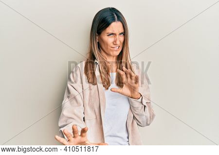 Brunette young woman wearing casual clothes disgusted expression, displeased and fearful doing disgust face because aversion reaction. with hands raised