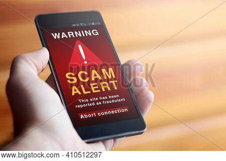 Closeup Of Male Hand Holding Modern Mobile Phone With Red Screen And Warning Symbol With The Text