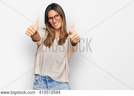 Young woman wearing casual clothes and glasses approving doing positive gesture with hand, thumbs up smiling and happy for success. winner gesture.