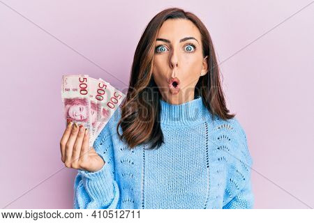 Young brunette woman holding 500 swedish krona banknotes scared and amazed with open mouth for surprise, disbelief face
