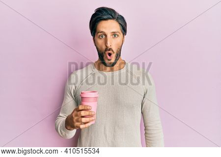 Young hispanic man drinking a take away cup of coffee scared and amazed with open mouth for surprise, disbelief face