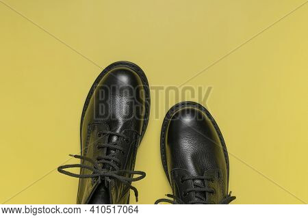 Fashionable Youth Black Leather Boots On Yellow Background Flat Lay Top View. Stylish Womens Mens Un