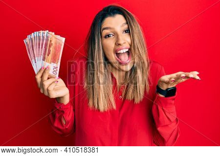 Beautiful brunette woman holding 100 norwegian krone banknotes celebrating achievement with happy smile and winner expression with raised hand