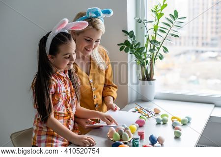Happy Easter. A Mother And Her Daughter Painting Easter Eggs. Happy Family Preparing For Easter. Cut