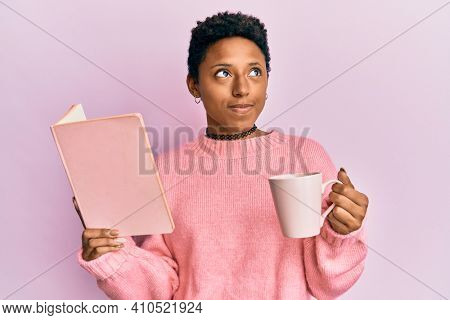 Young african american girl reading a book and drinking a cup of coffee smiling looking to the side and staring away thinking.
