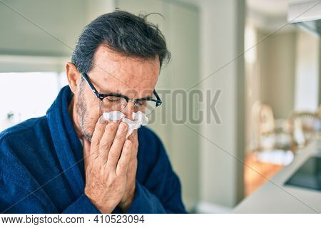 Middle age man feeling sick with cold and fever at home, ill with flu disease