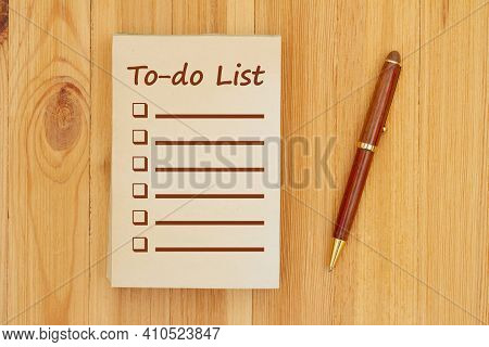 To-do List On An Old Paper Notepad With Pen On Wood Desk