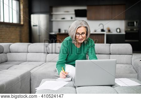 Busy Active Mature Businesswoman Freelancer In Glasses And Green Jumper Sitting On The Couch In Fron