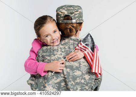 Cheerful Kid With American Flag Embracing Mother In Military Uniform Isolated On Grey