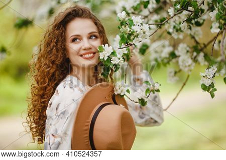 Young Beautiful Woman In Blooming Garden. Pretty Girl Wearing Brown Hat Smiling And Being Happy Touc