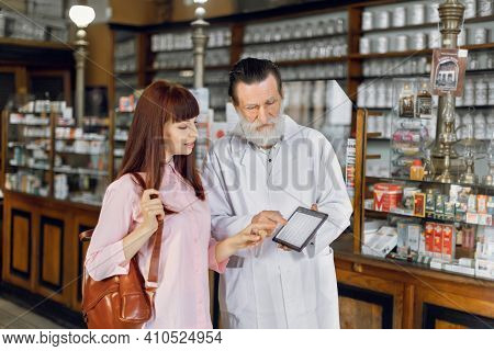 Pharmacy And Prescription Concept. Senior Caucasian Man Pharmacist With Tablet, Reading Patients Pre
