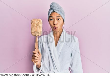 Young chinese woman wearing shower towel cap and bathrobe holding sponge scared and amazed with open mouth for surprise, disbelief face