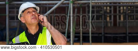 Panorama thoughtful male builder foreman, construction worker, contractor or architect on building site holding black clipboard and talking on his cell phone panoramic web banner header