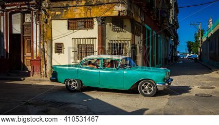 Havana, Cuba, July 2019, View Of A Green Old Classic American Car With Passengers Driving Through At