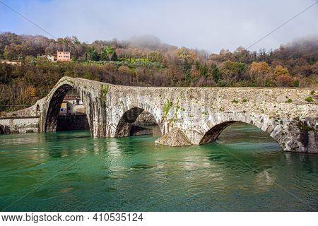 Devil's Bridge over the Cercchio River. Medieval bridge with magnificent architecture. Italy. Province of Tuscany. Outskirts of Bagni di Lucca