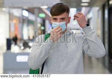 Portrait Of Handsome Guy, Young Man Putting On Sterile Medical Mask On His Face Against Virus, Coron