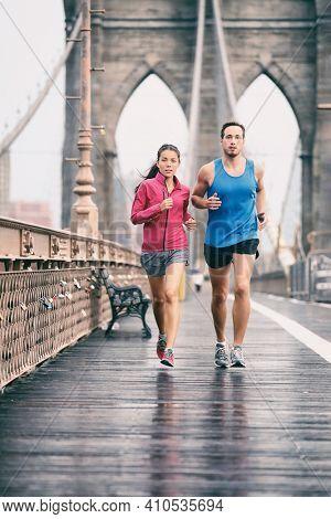 New York city runners athletes training jogging on Brooklyn Bridge for Marathon race, fit couple on outdoor summer run jog. Vertical background.