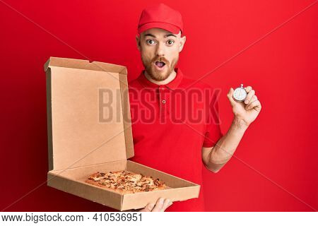 Young redhead man wearing delivery uniform holding pizza box and countdown clock afraid and shocked with surprise and amazed expression, fear and excited face.