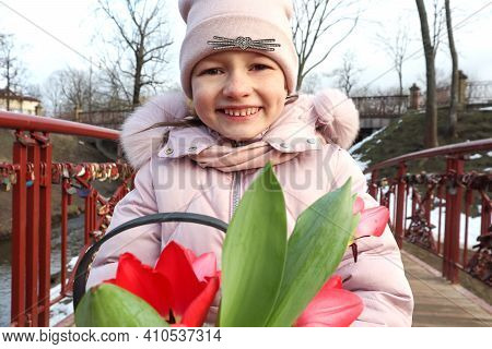 Happy Eight-year-old Girl With Scarlet Tulips On The Street, Close-up