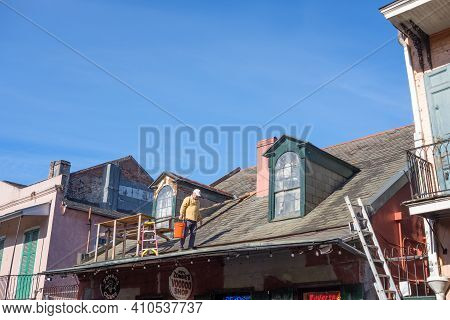 New Orleans, La - January 28: Painter Walks Back To Ladder On Rooftop In The French Quarter On Janua