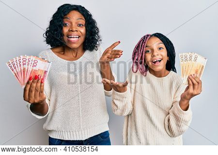 Beautiful african american mother and daughter holding norwegian krone banknotes celebrating achievement with happy smile and winner expression with raised hand