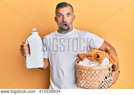 Middle age handsome man holding laundry basket and detergent bottle afraid and shocked with surprise and amazed expression, fear and excited face.