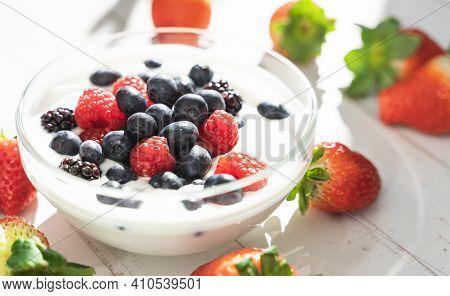 Yogurt In A Glass Bowl With Different Berries. Strawberries, Raspberries, Blueberries