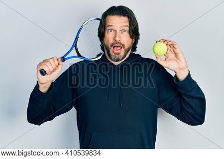 Middle age caucasian man playing tennis holding racket and ball afraid and shocked with surprise and amazed expression, fear and excited face.