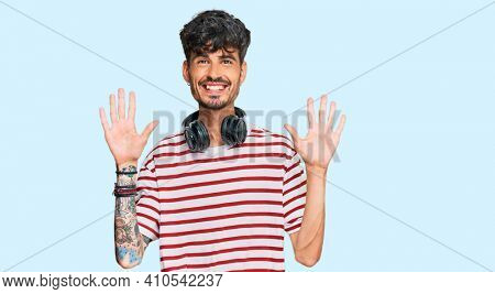 Young hispanic man listening to music using headphones showing and pointing up with fingers number ten while smiling confident and happy.