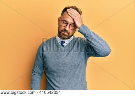 Handsome middle age man wearing glasses surprised with hand on head for mistake, remember error. forgot, bad memory concept.