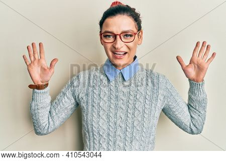 Young caucasian woman wearing casual clothes and glasses showing and pointing up with fingers number ten while smiling confident and happy.