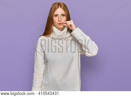 Young irish woman wearing casual winter sweater mouth and lips shut as zip with fingers. secret and silent, taboo talking