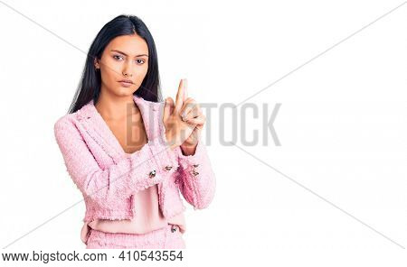Young beautiful latin girl wearing business clothes holding symbolic gun with hand gesture, playing killing shooting weapons, angry face