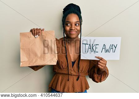 African american woman with braided hair holding take away paper bag smiling looking to the side and staring away thinking.
