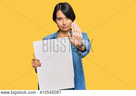 Beautiful young woman with short hair holding blank empty banner with open hand doing stop sign with serious and confident expression, defense gesture