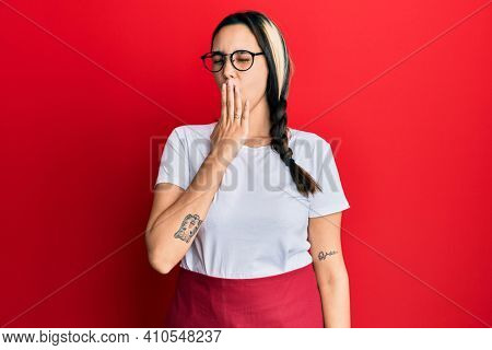 Young hispanic woman wearing professional waitress apron bored yawning tired covering mouth with hand. restless and sleepiness.