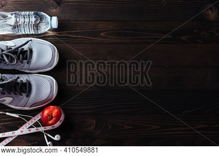 Pair Sports Shoes, Headphones, Apple And Water Bottle On Black Wood Table Background, Gray Sneakers