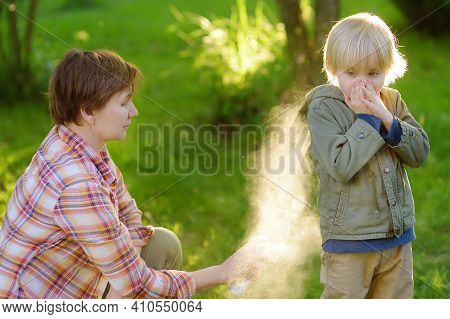 Woman Spraying Insect Or Mosquito Repellents On Little Boy Before A Walk In The Forest. Protect Chil