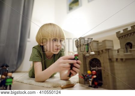 Little Child Is Playing With Toy Prototype Medieval Castle. Knights And Battles - Favorite Game For