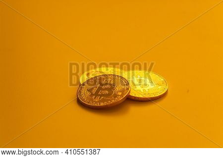 Three Yellow Bitcoin Beans Laying On Flat Surface