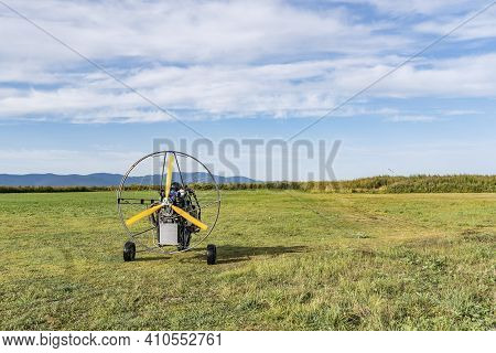 Moto-paraglider On Green Grass With Blue Sky.