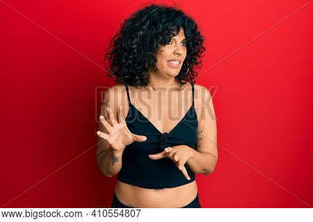 Young hispanic woman wearing casual style with sleeveless shirt disgusted expression, displeased and fearful doing disgust face because aversion reaction. with hands raised